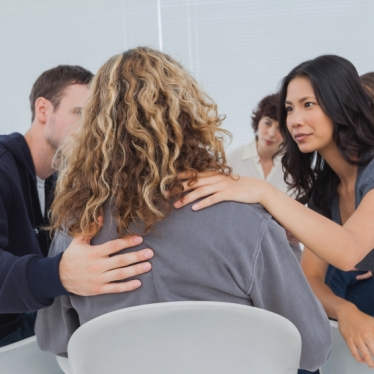 Patients encouraging a woman who is crying during group therapy session